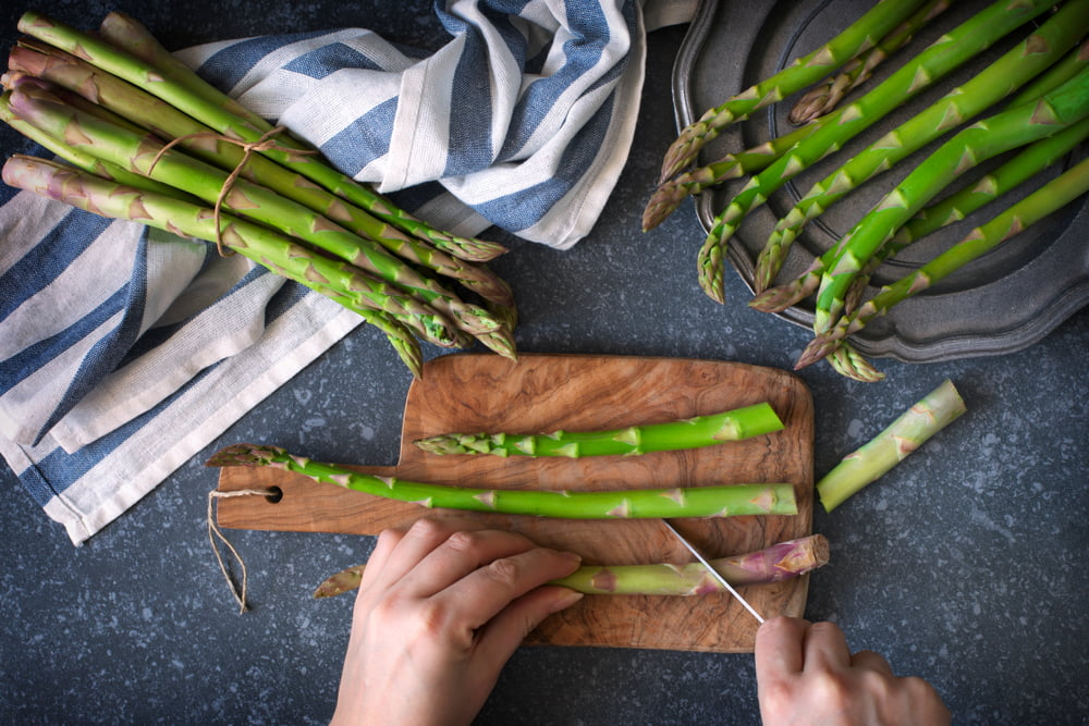 Hands cutting asparagus on chopping board