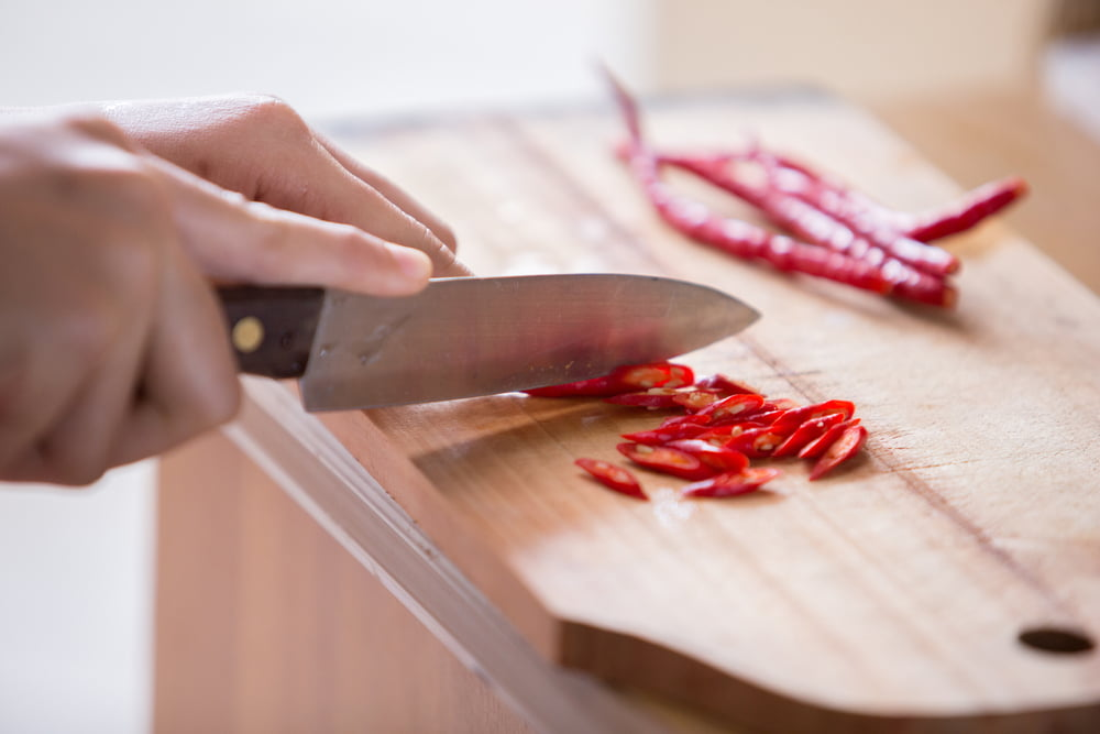 Slicing chillies on chopping board