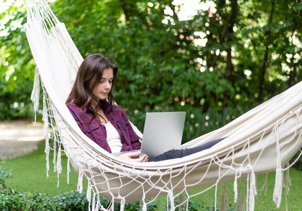 woman-with-laptop-in-a-hammock-in-garden